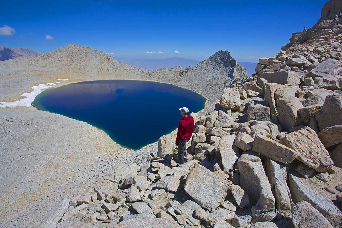 Don checks out the blue depths of Tulainyo Lake from the top ofRussell-Carillon Col.