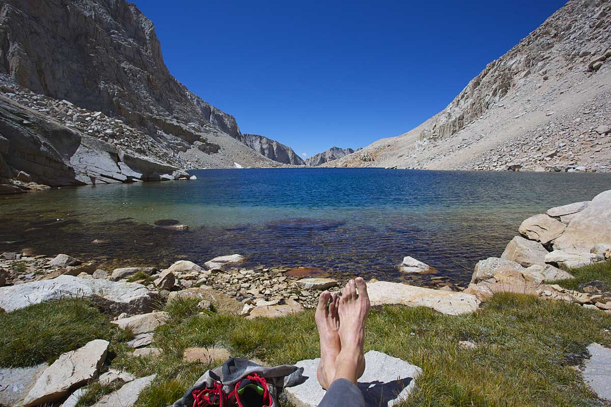 Taking a rest at the uppermost Crabtree Lake, just west of Crabtree Pass. At 12,119 feet, this isolated lake is the first water source since Iceberg Lake (i.e. summiting Mt. Whitney and traversing the Whitney Crest). It has a small patch of grass on its eastern shore. The lake is a welcome respite after the dusty 1500 foot descent from the crest.