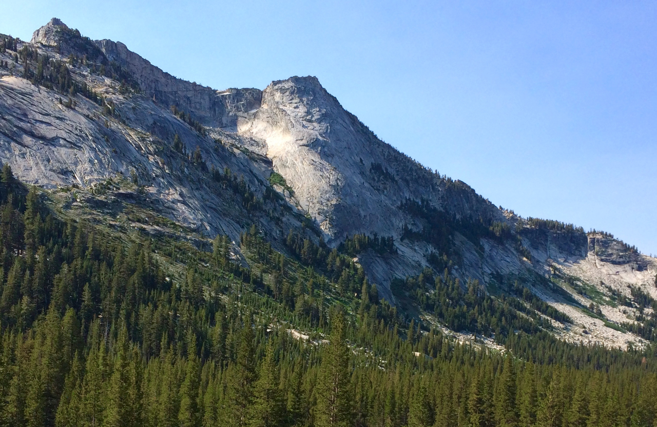 The northwest buttress of Tenaya Peak is the obvious buttress in the center of the photo. The route starts near the horizontal ledge, covered with trees at the base of the buttress. It follows near the sun/shade line to about halfway up, then angles to the left, into the sun, finishing near the left edge of the nearly flat summit plateau. From the parking lot at the east end of Tenaya Lake, expect to spend 30 to 40 minutes on the approach.