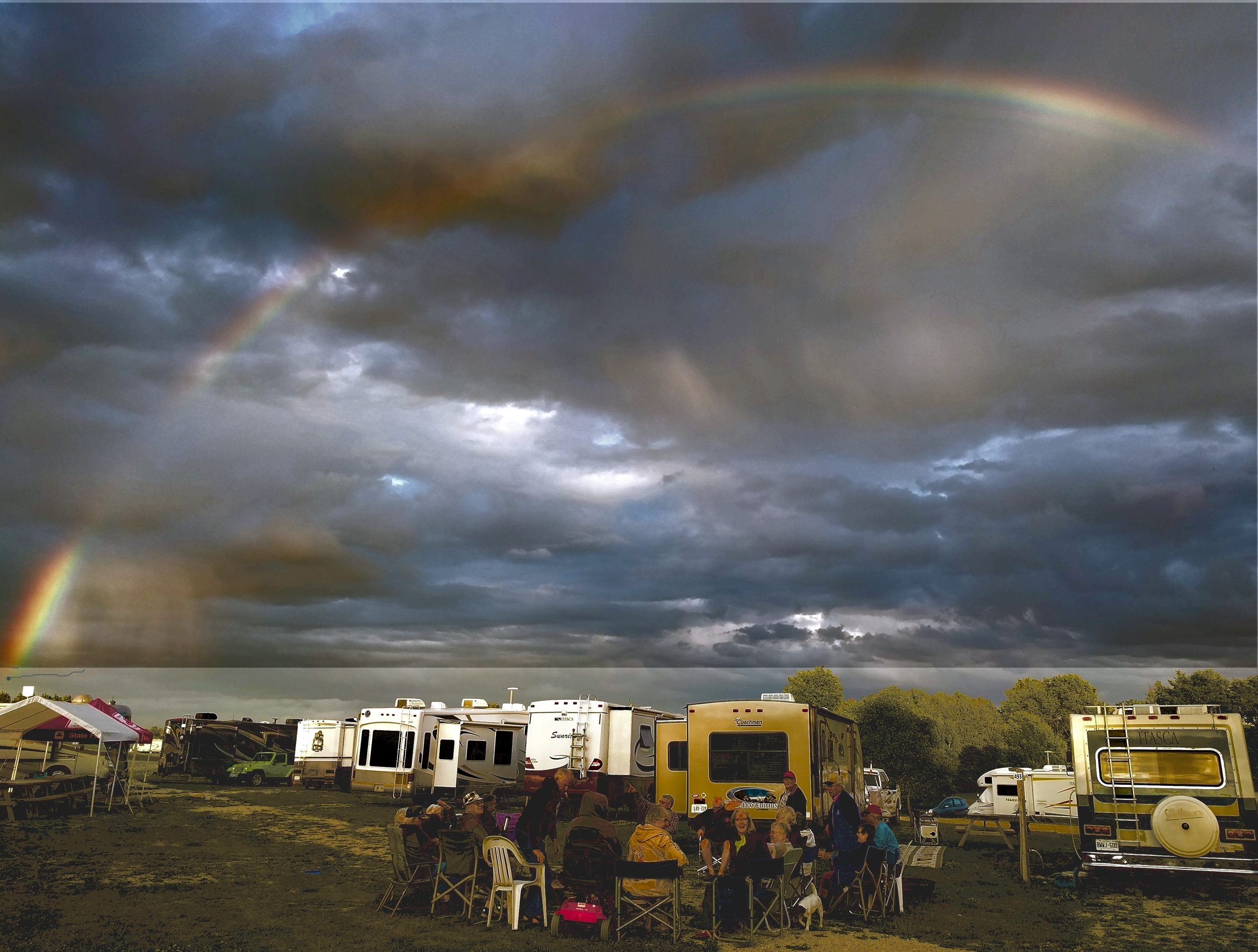 A rainbow hovers above as the group gathers around a warm fire.