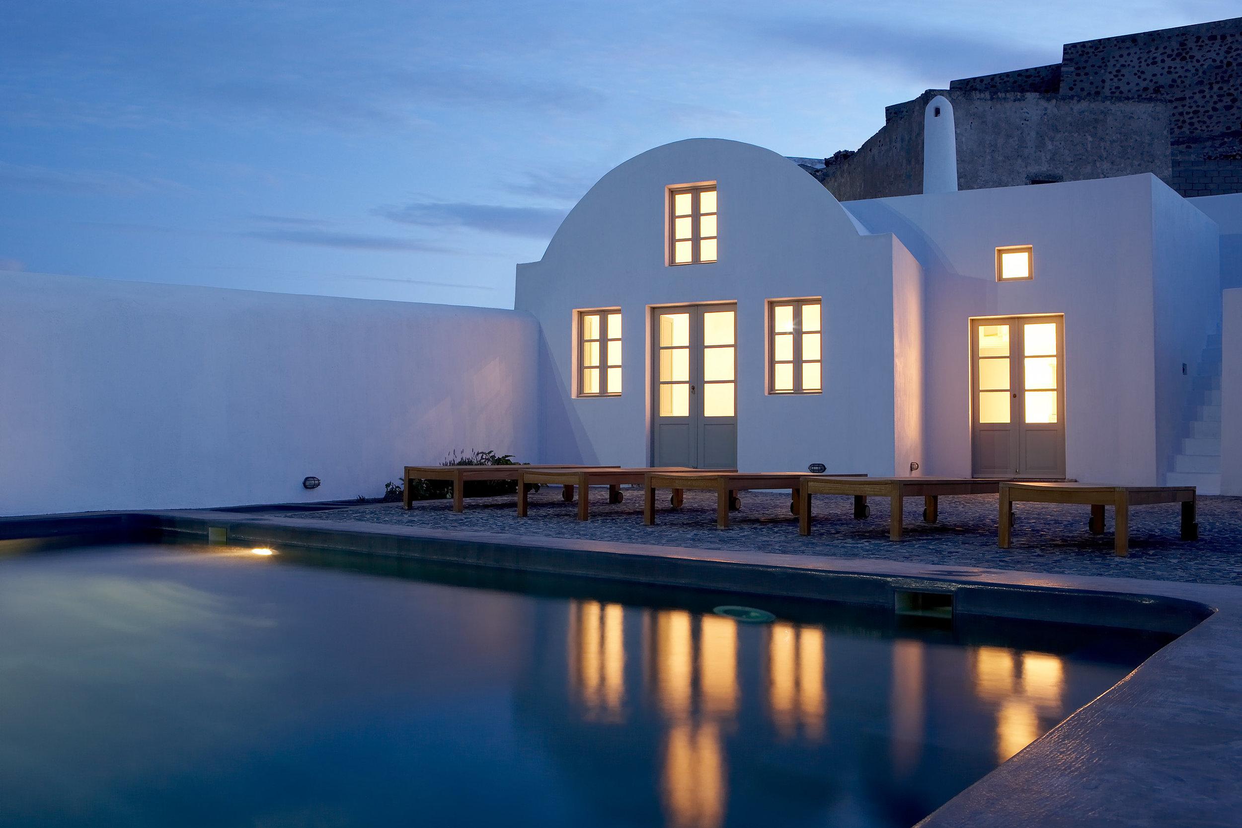 luxury-villa-santorini-greece-old-factory-loft-style-leisure-pool-public-dining-dusk.jpg