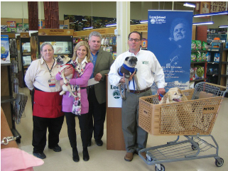 """A PETCO employee, Ed Edmunsen, PETCO's LI District Manager, Susan Kaufman and Paule Pachter, Executive Director of Long Island Cares, with some four-legged friends, at the opening of PETCO's """"We Are Family Too"""" program to benefit Long Island Cares"""
