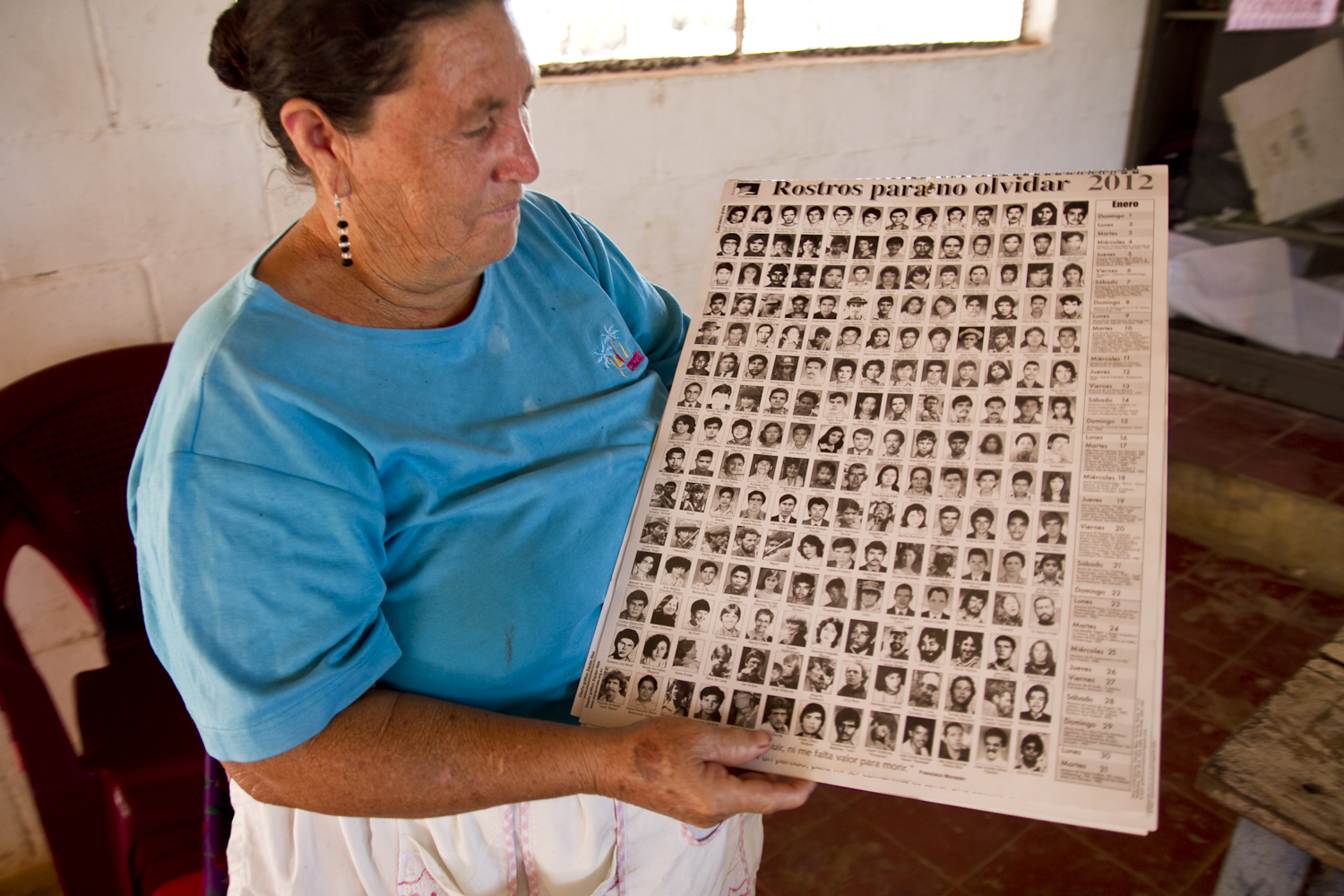 Felicita Osorio Alvarado holds a calendar with photos of the Salvadorans killed throughout the 12-year civil war. Alvarado  lost three brothers and her father in the conflict.