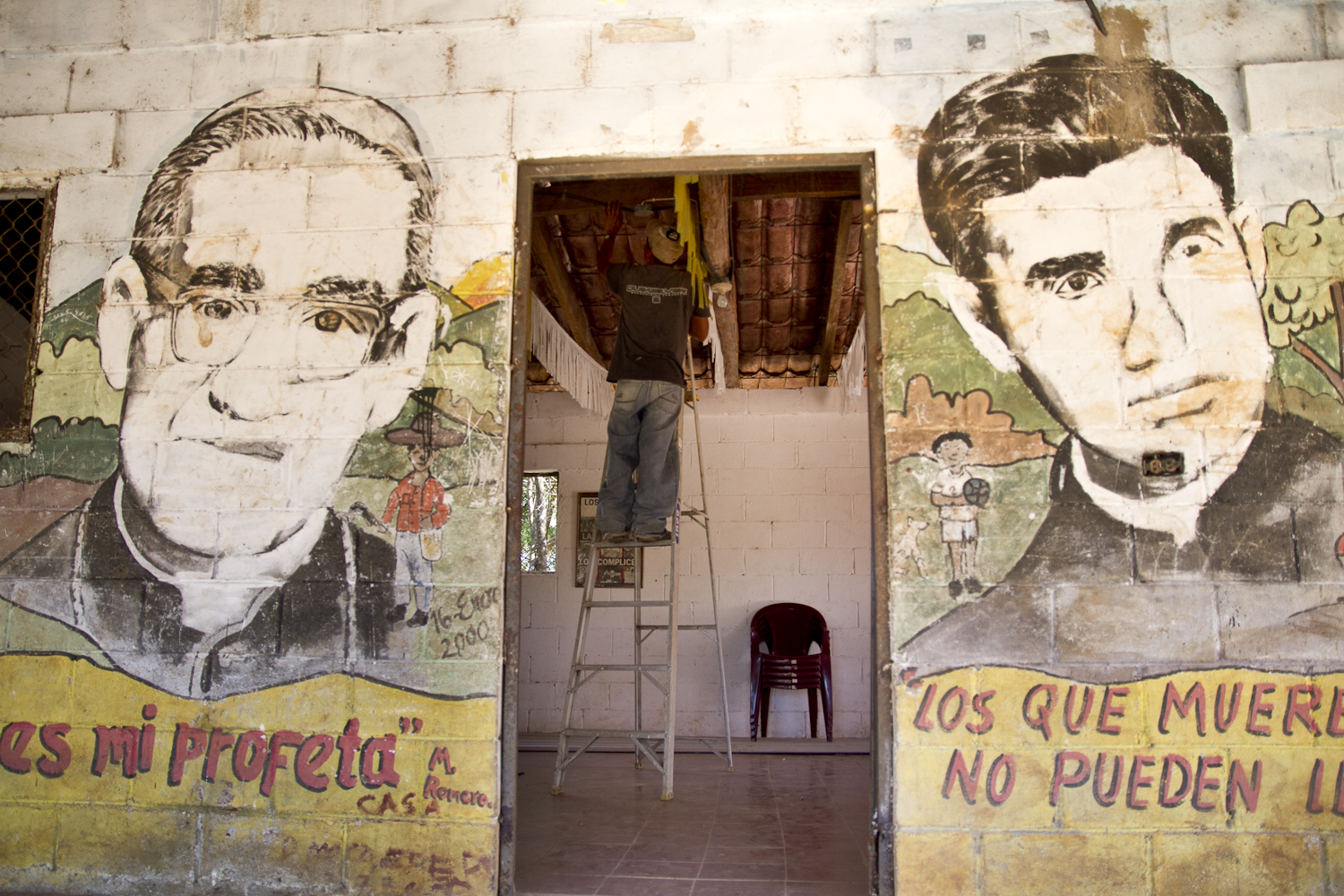 """The images of Óscar Romero and  Father Napoleón Macías adorn the side of Amatitán's community center.  Strong advocates for human rights and changes in the government, both  were assassinated by military forces. Below their likenesses reads two  quotes: """"El pueblo es mi profeta"""" (The people are my prophet) and """"Los  que mueren por la vida no pueden llamarse muertos"""" (Those who die for  life cannot be called dead)."""