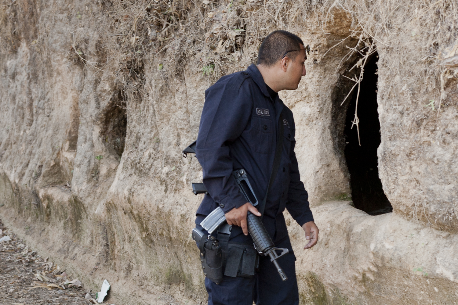 A police officer examines a hole in the road wall, carved during the  military invasion of the town. Civilian families used them as makeshift bomb  shelters for their children, to protect them from the 500-pound  explosives dropped by government planes.