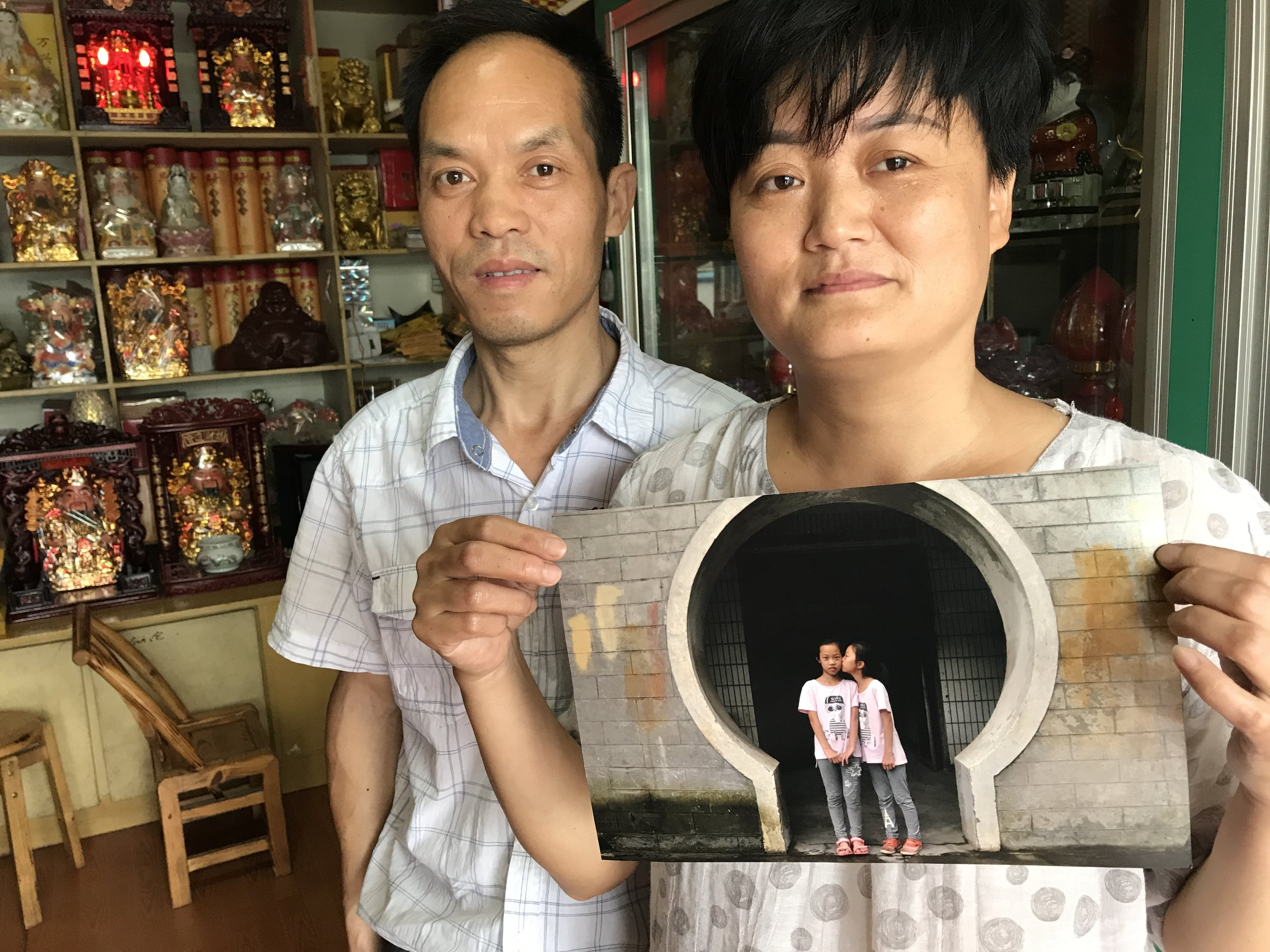 Xin Xian Shou and Zhu Yuan e with the 2016 portrait of their daughters, during a 2017 visit.