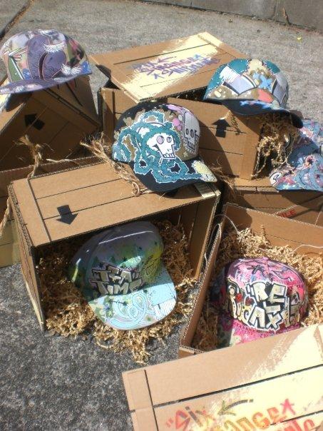 Six Strange Shipments    2007 Acrylic on baseball caps in handmade crane design cardboard packaging.