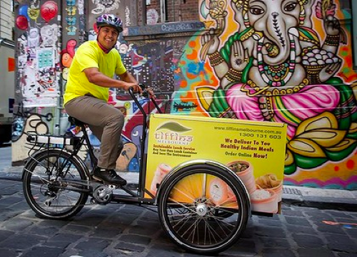 The Ag e, 11 February 2012, Meals on wheels bring curry in hurr y  EACH week day in Mumbai some 5000 tiffin-wallahs set off by bicycle across the city to deliver office workers their lunches. Now tiffin-wallahs have come to Melbourne in the form of the brightly coloured tricycles of Tiffins Melbourne. The logistical miracle which is the tiffin delivery system in Mumbai involves the tiffin-wallahs picking up home-cooked lunches stored in stacked metal containers known as tiffins from each worker's home....