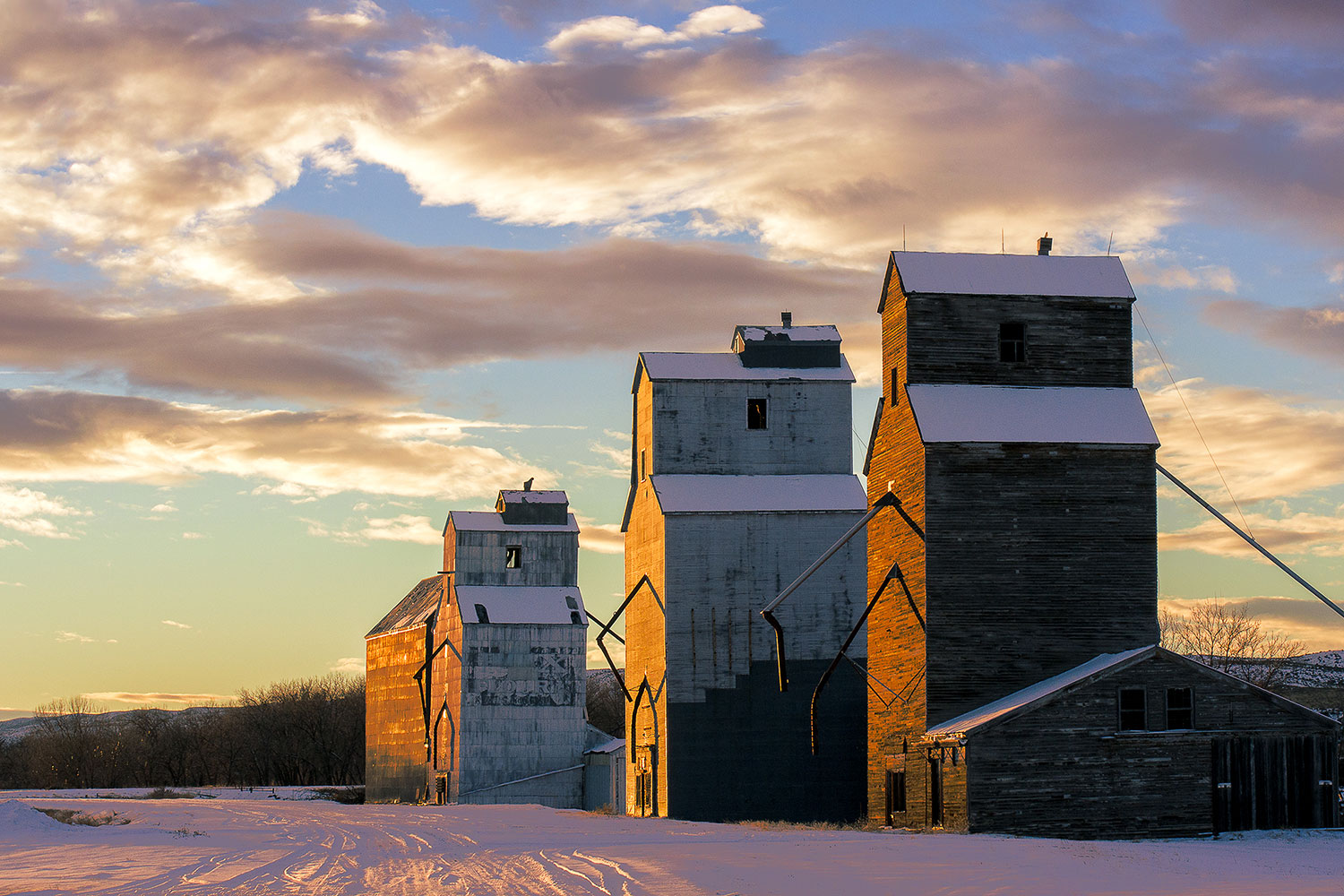 A row of grain elevators illuminated by the last light of the day in what is downtown Loma, Montana...population 92. Photograph was taken with the Samsung NX300 mirrorless camera.     → Buy This Print