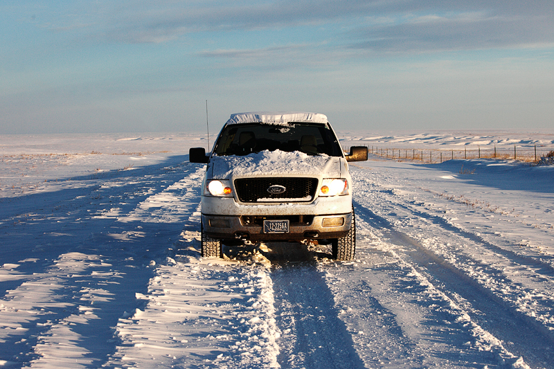 My cold Ford pick-up truck on snow covered road somewhere deep in the Montana hinterland. Here, south of Cleveland, Montana, I was many, many miles from another person. Just another day in paradise.  → License Photo