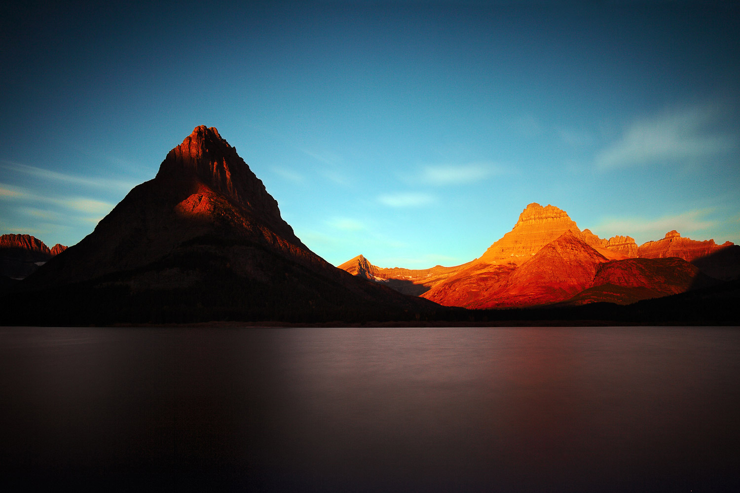 The sun rising over Mount Grinnell and the Rocky Mountains at Glacier National Park.      → Buy This Print