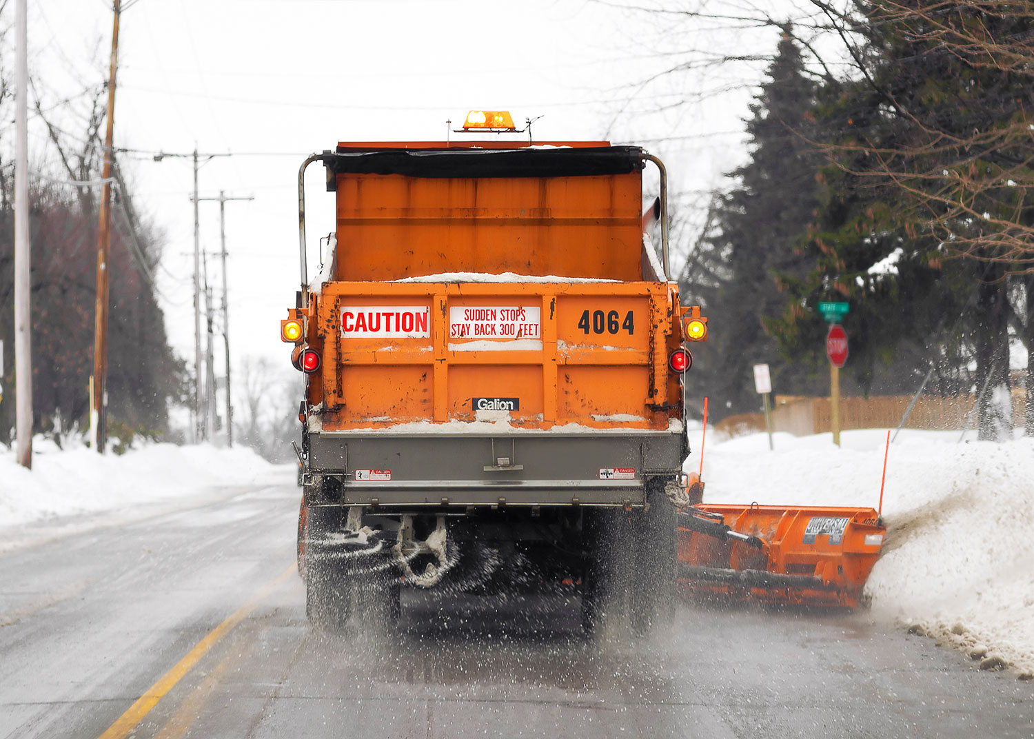 A snow plow removing snow and spreading some salt.  → License Photo
