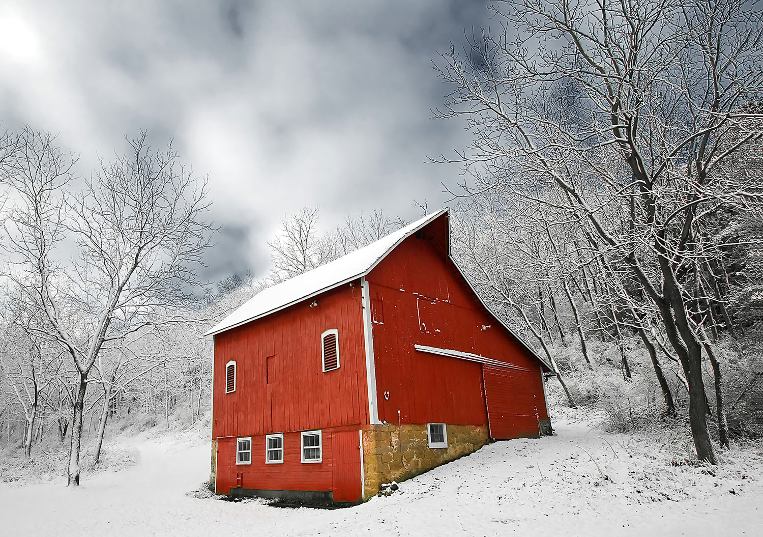 Freshly fallen snow clings to a little red barn on a small farm in the trees.  → Buy a Print