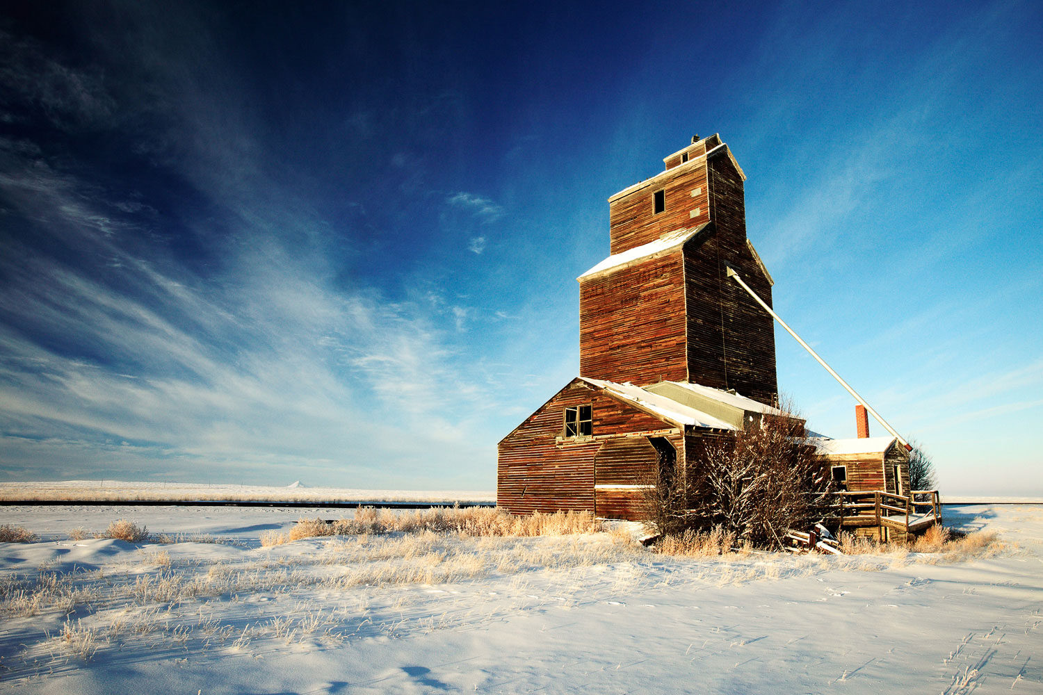 An old, broken down grain elevator sits quietly in the cold western snow.  → Buy a Print