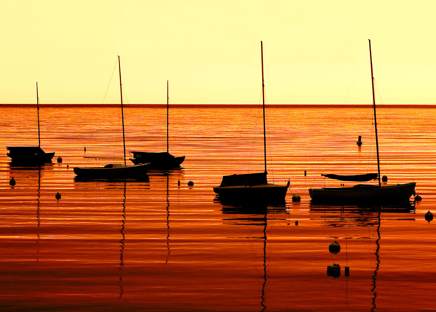 The morning sun casts an orange hue over Rockport Harbor in Rockport, Massachusetts.   → Buy a Print