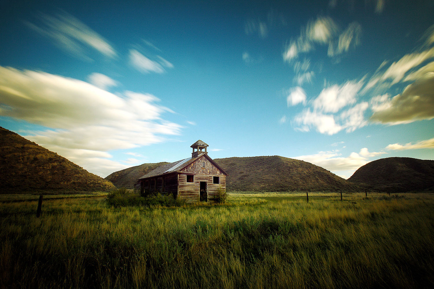 An old, weathered schoolhouse or church tucked between the hills outside of Loma, Montana.  → Buy a Print