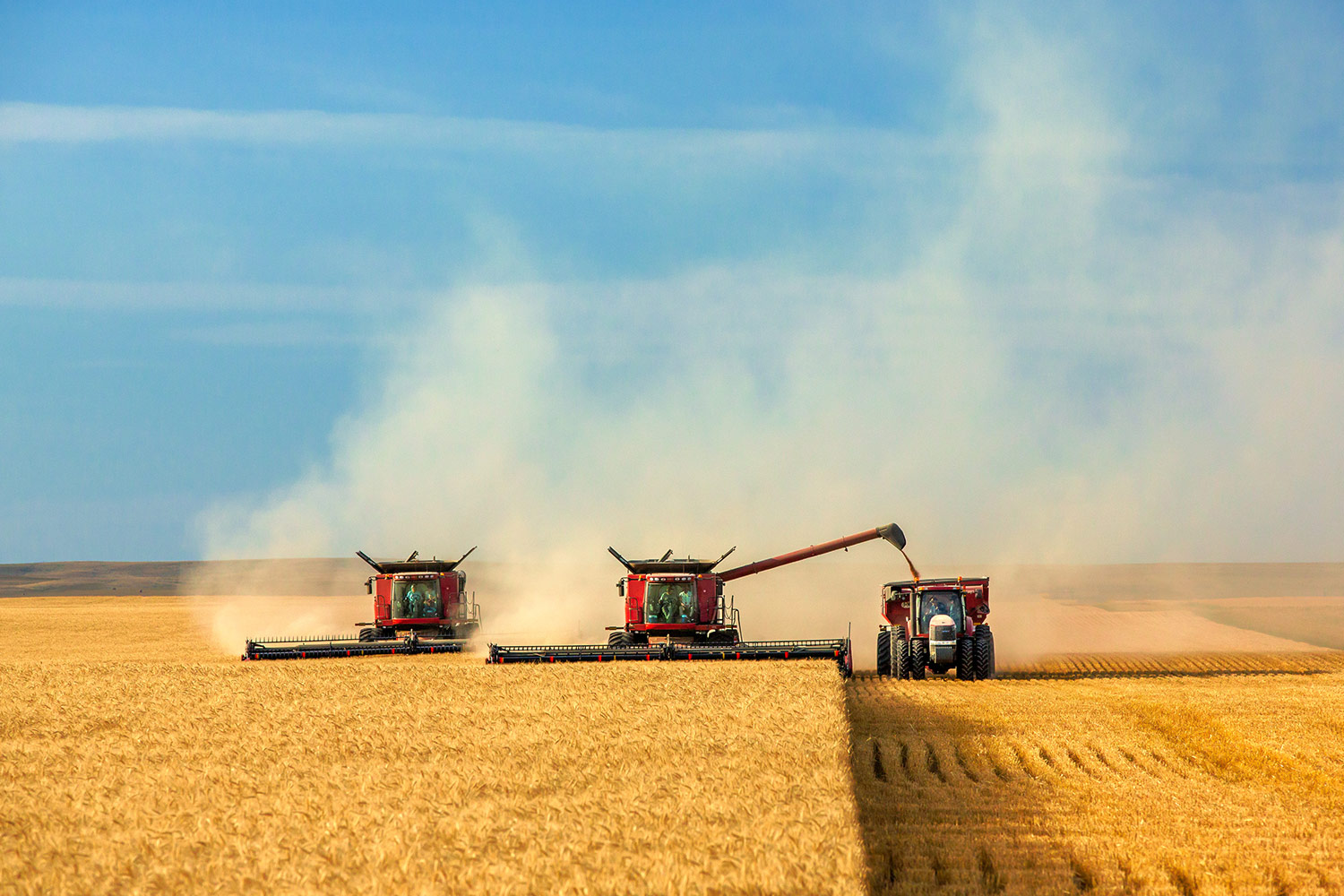 Combines and Tractor Working Together
