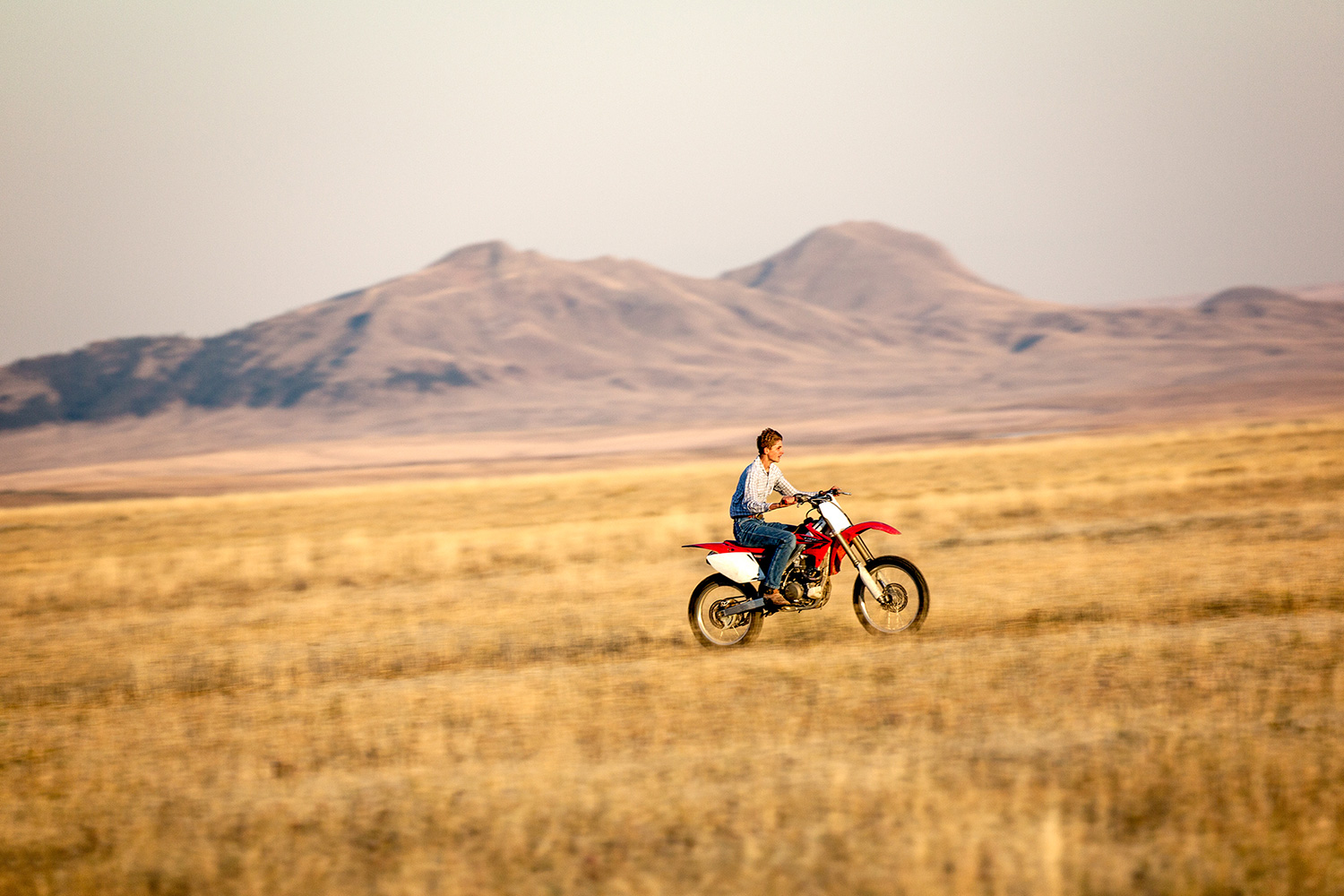A teen riding his motorcycle fast across the open plains near Cleveland, Montana.    → License Photo