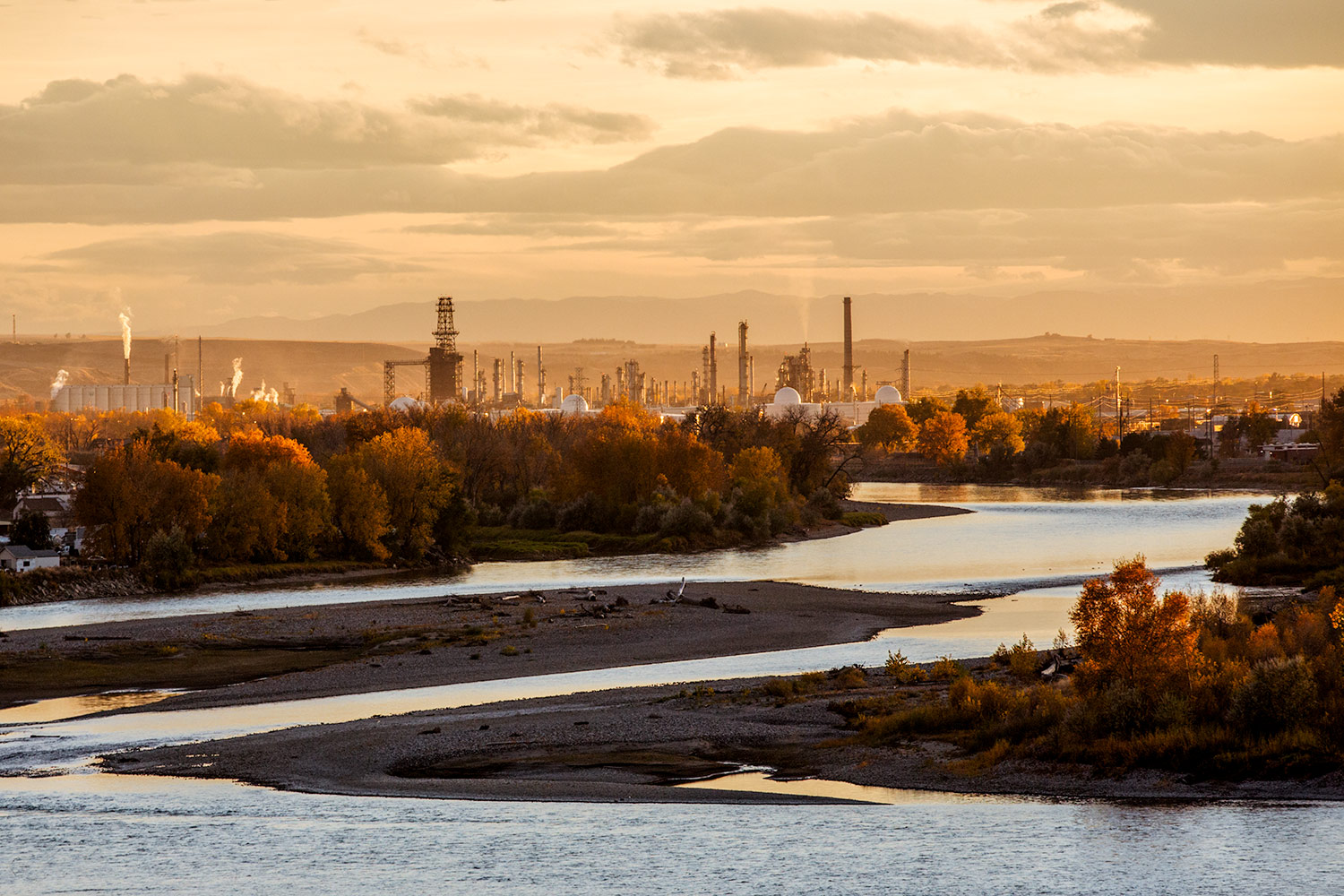 The view looking south over the Yellowstone River towards autumn trees and an oil refinery in Billings, Montana at sunset.   → Buy a Print    or   License Photo