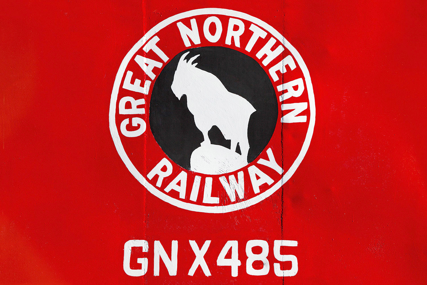 A close-up of the Great Northern Railway logo on the side of a caboose in Havre, Montana which is painted in bright, bright red.  → Buy a Print    or    License Photo