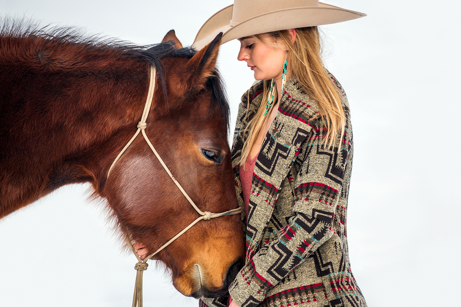 A cowgirl rubs the chin of her horse on a ranch outside of Bozeman, Montana.   → License Photo