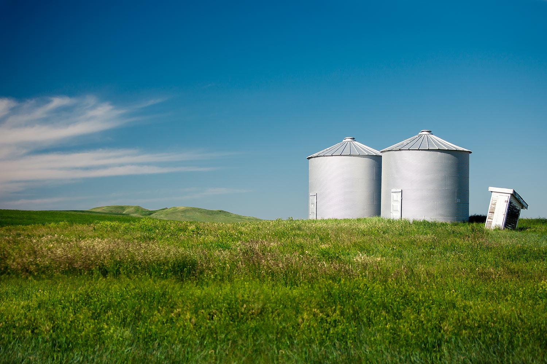 A pair of grain elevators sit alone on top of a ridge near Shonkin, Montana.  → Buy a Print
