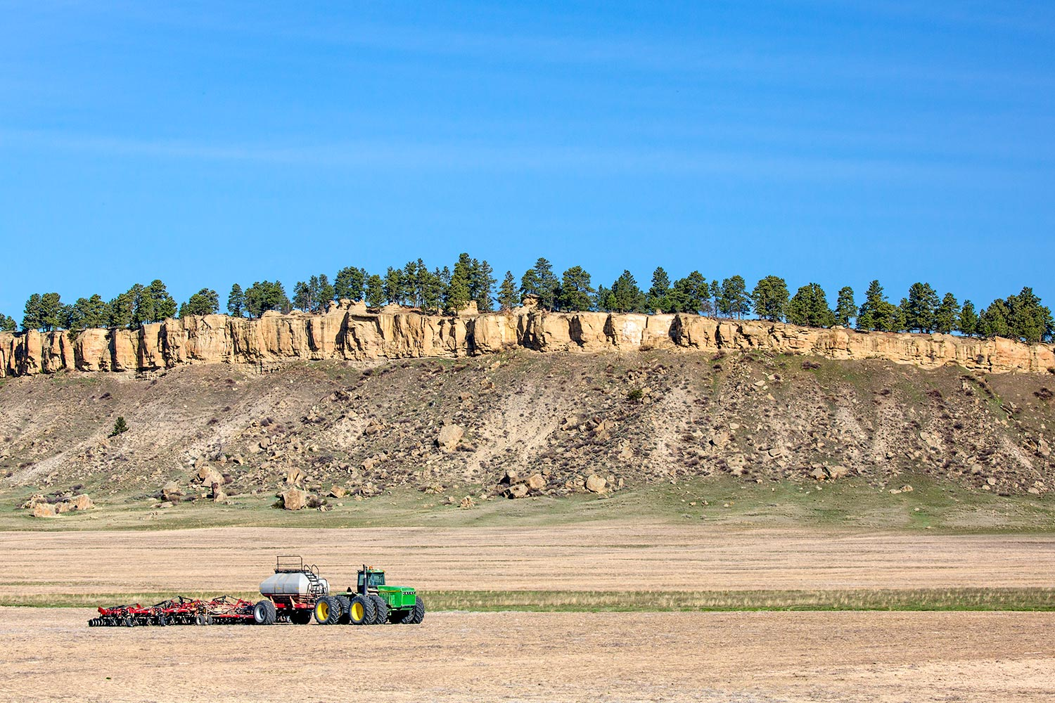 Farm equipment parked by the rimrocks near Ryegate, Montana.  → Buy a Print  or   License Photo