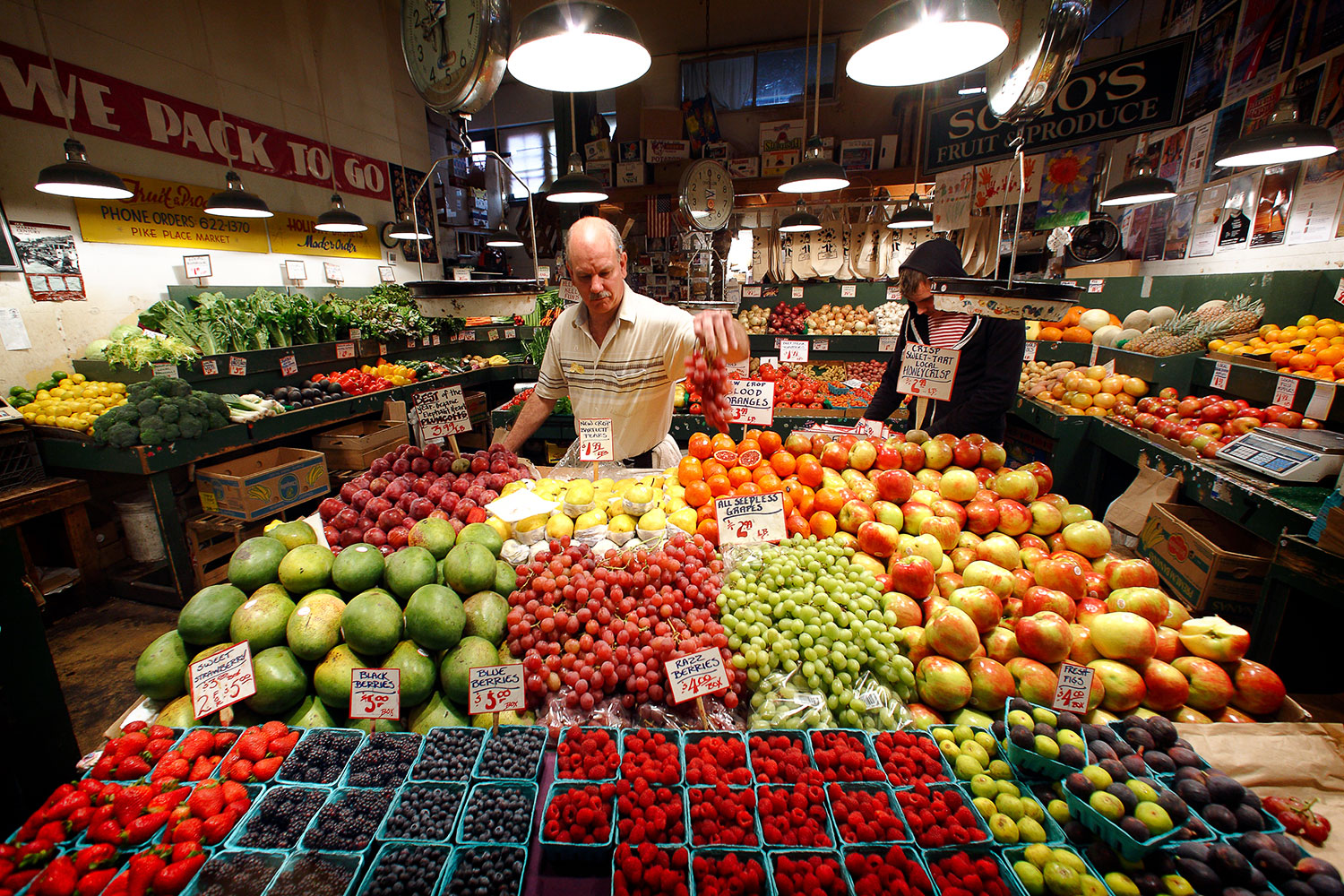 A produce vendor setting out more grapes at Pike Place Market in Seattle, Washington.    → License Photo