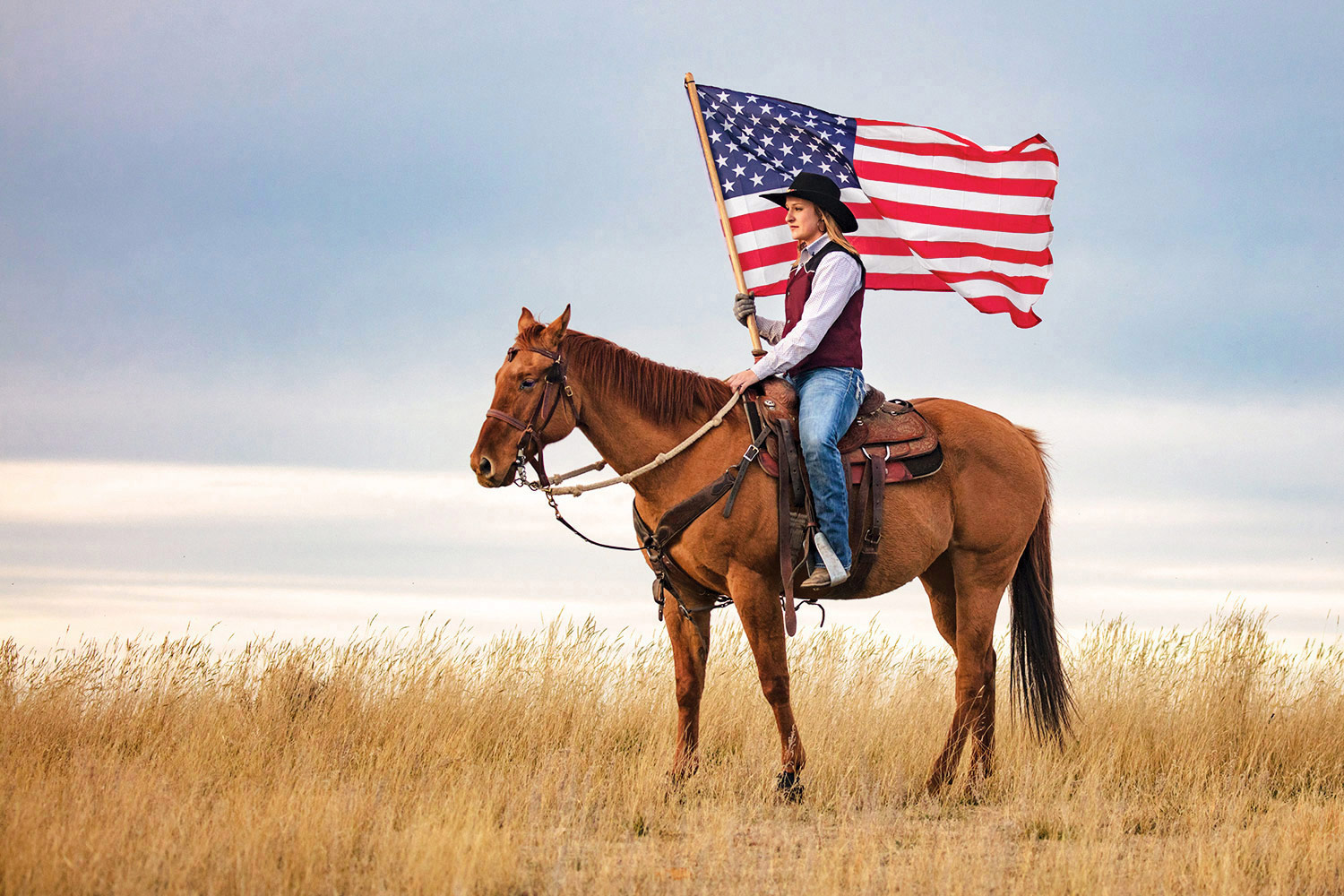 A cowgirl riding horseback with an American flag near Box Elder, Montana. To see more cowgirl photos click here:  Cowgirl Photos