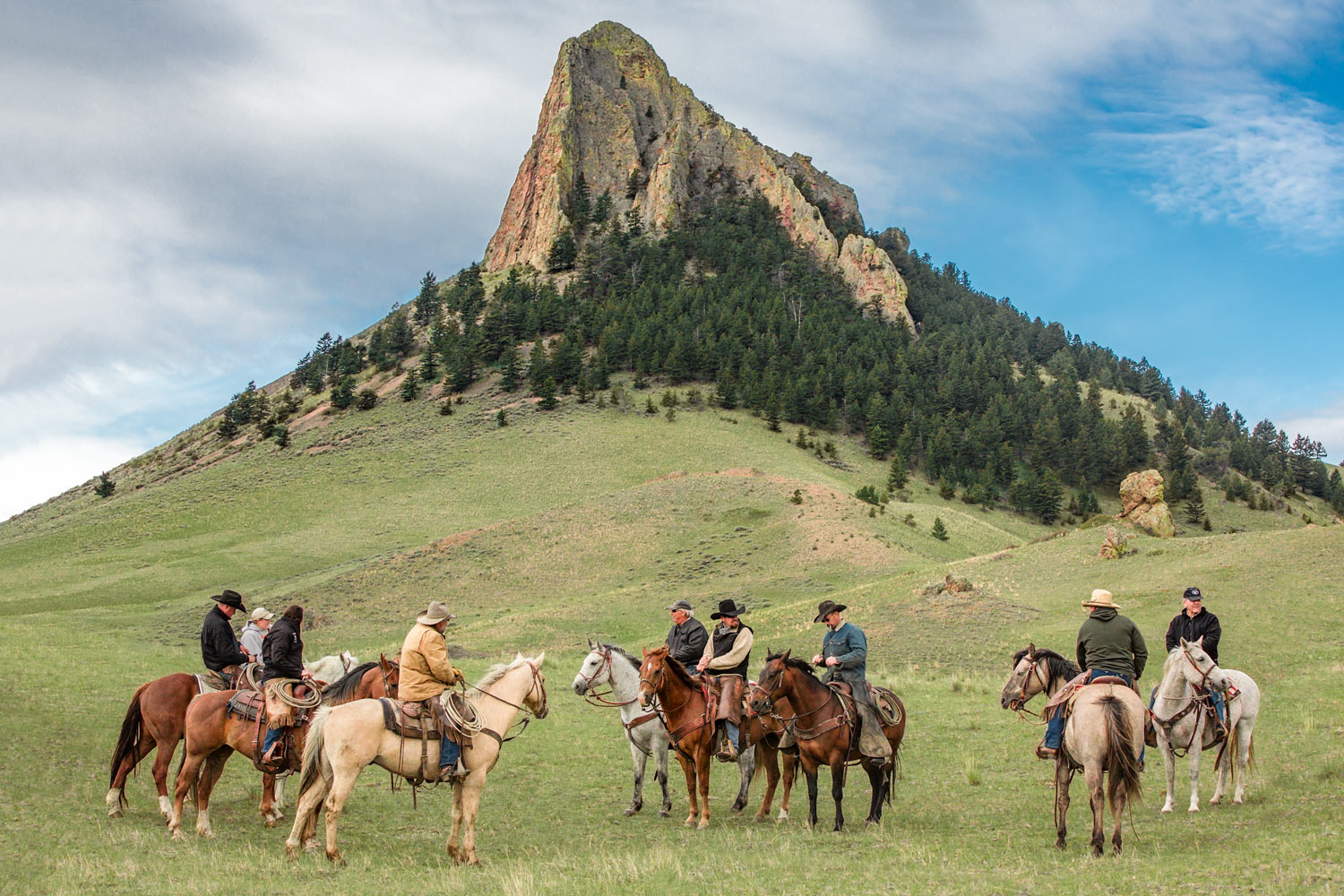 Cowboys and cowgirls gather at the base of Birdtail Butte near Cleveland, Montana.  → License Photo