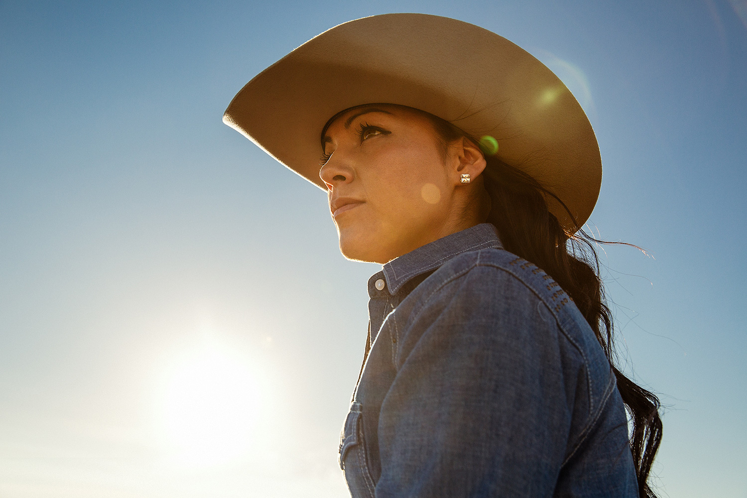 A cowgirl posing in the sun near Fort Belknap, Montana.  → License Photo