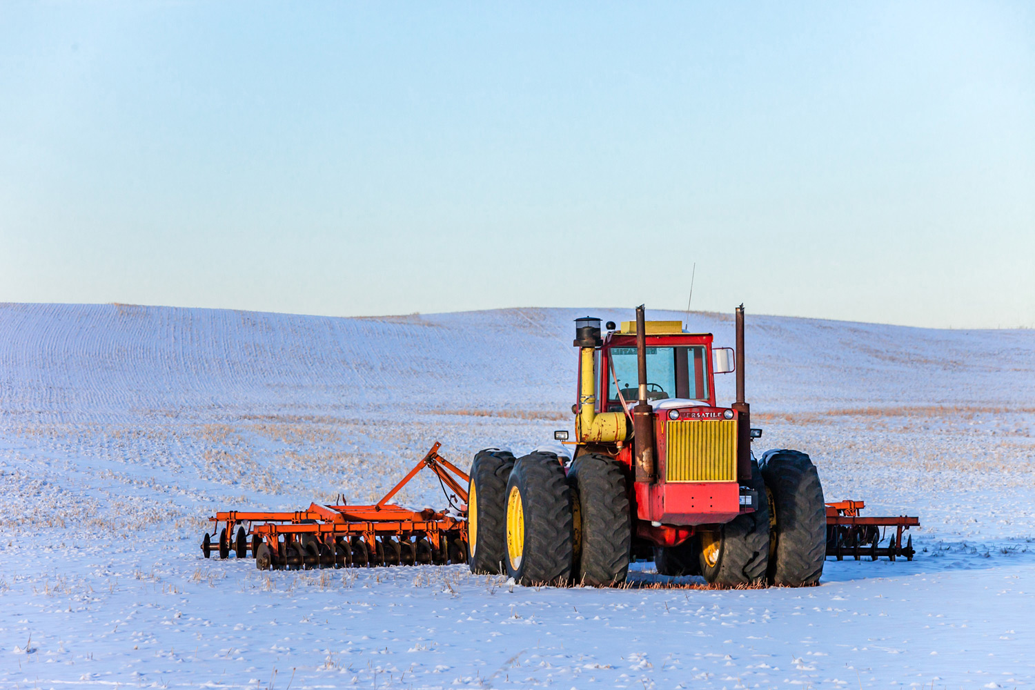 An old Versatile 900 tractor stands out in a field of snow near Fort Benton, Montana.   → License Photo