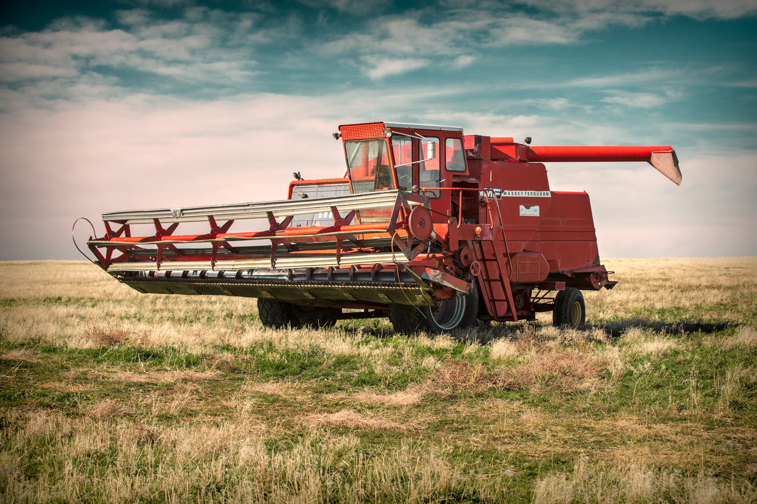 An old Massey Ferguson 760 combine sits alone high atop a ridge in the middle of a field near Stanford, Montana.  → License Photo