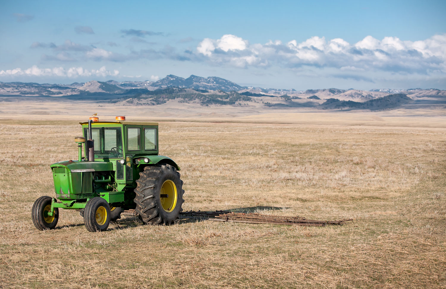 An old John Deere 4020 tractor hooked to a harrow near Cleveland, Montana.  → License Photo