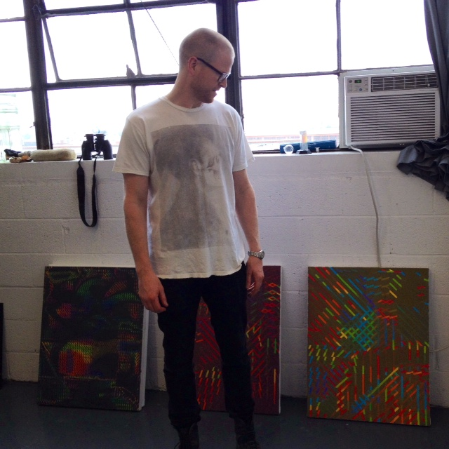 Artist Jeff Fichera admiring his paintings for a brief moment among the chaos of open studios.