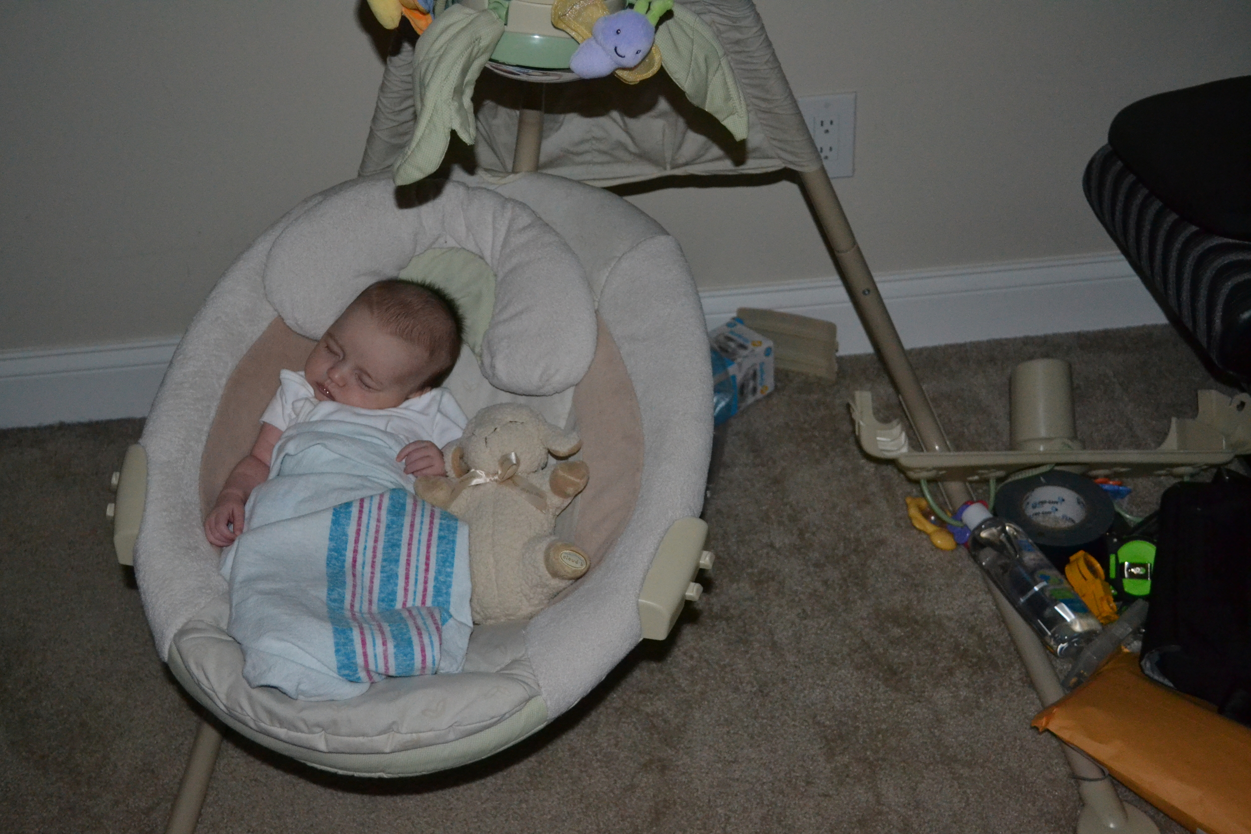 Daphne snuggling with Sleep Sheep in her swing