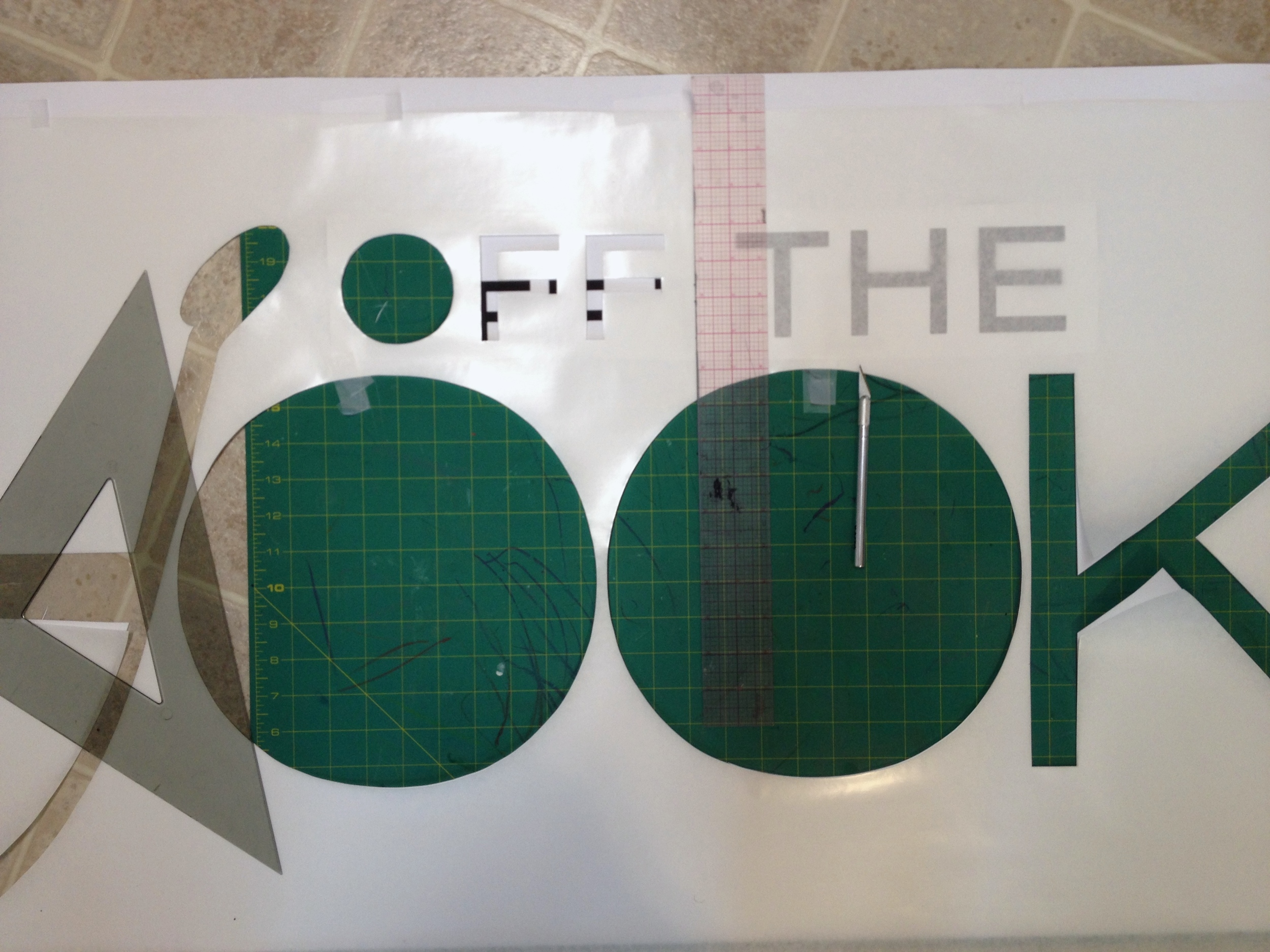 Cutting out the logo using frisket paper, X-acto blades, a cutting mat and straight edges.