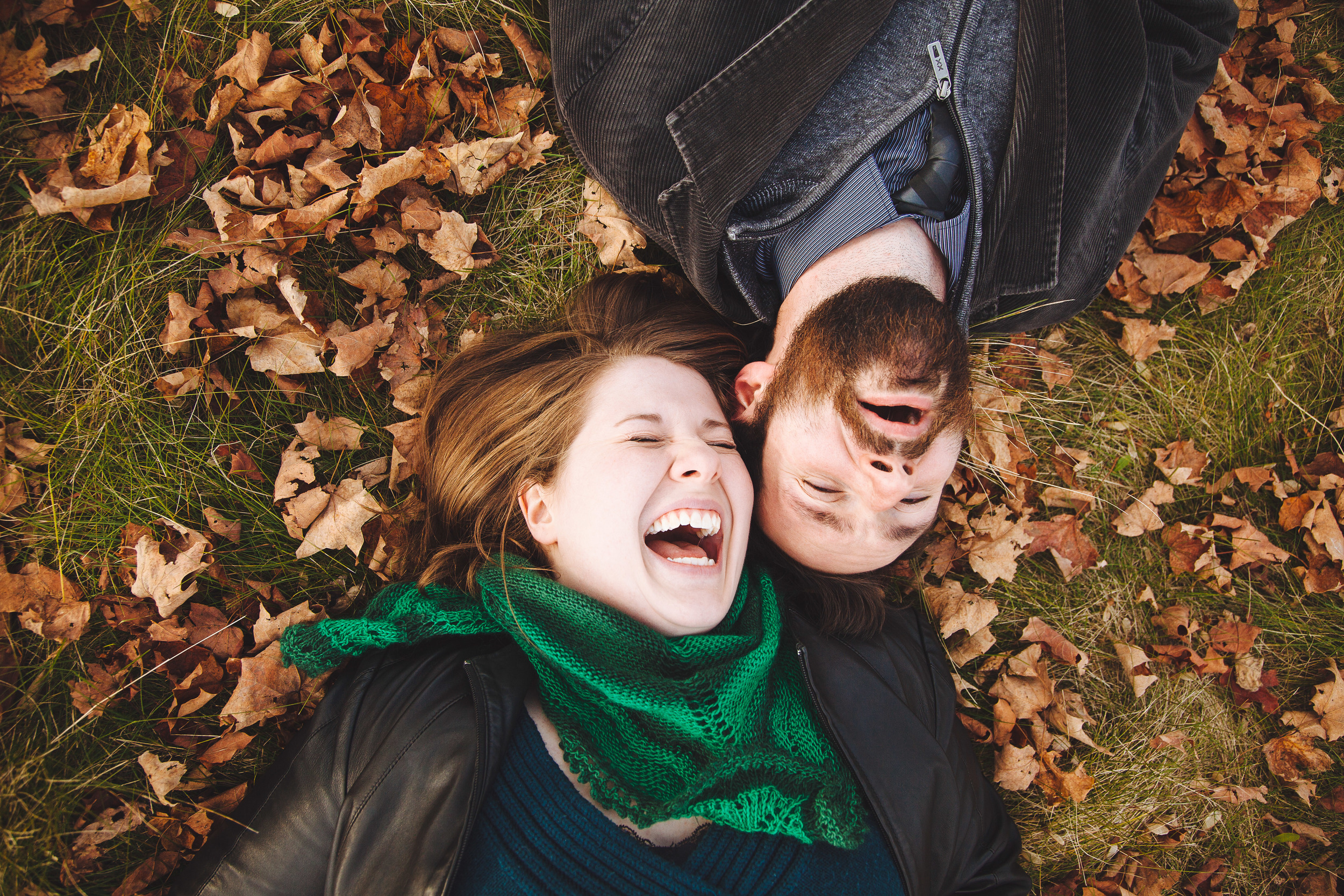 On the ground laughing in the leaves during a fall engagement session in Ottawa Ontario