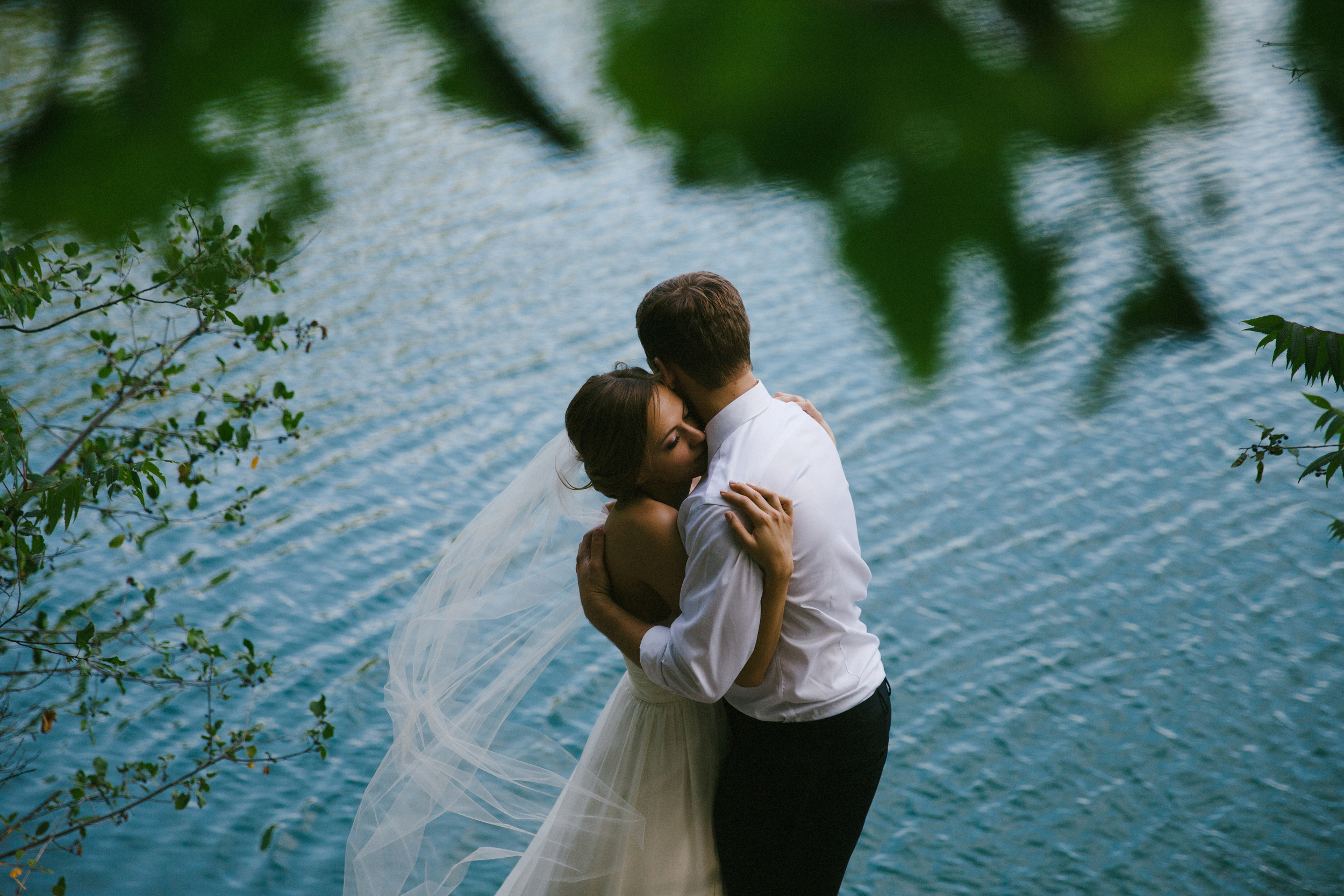a loving couple embrace in front of pink lake in gatineau park after saying i do