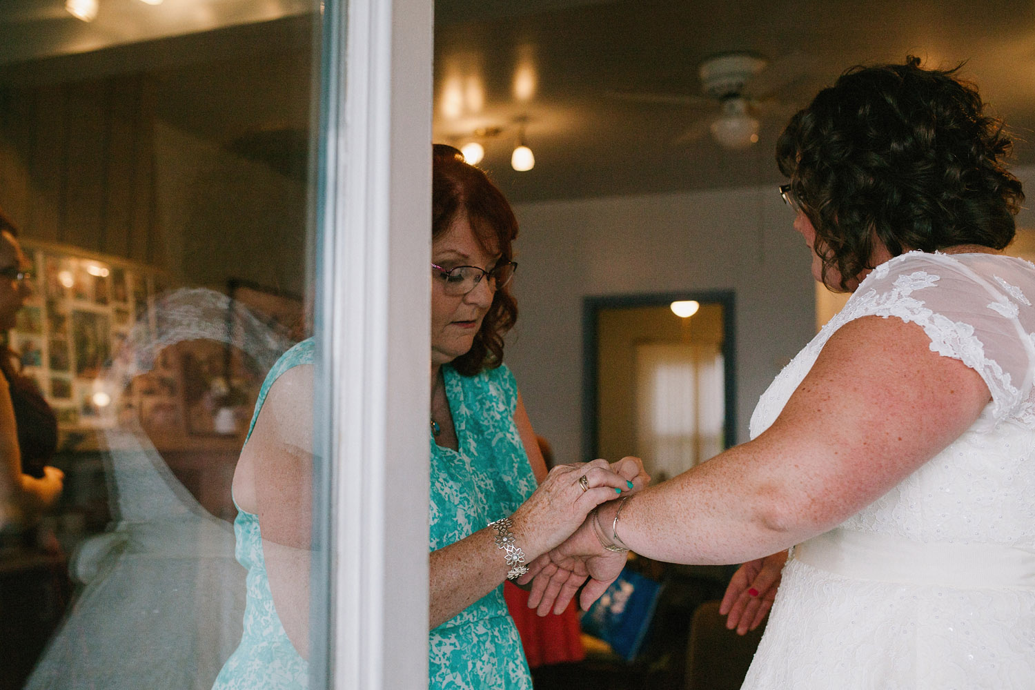 mom helps bride put on wedding jewellery