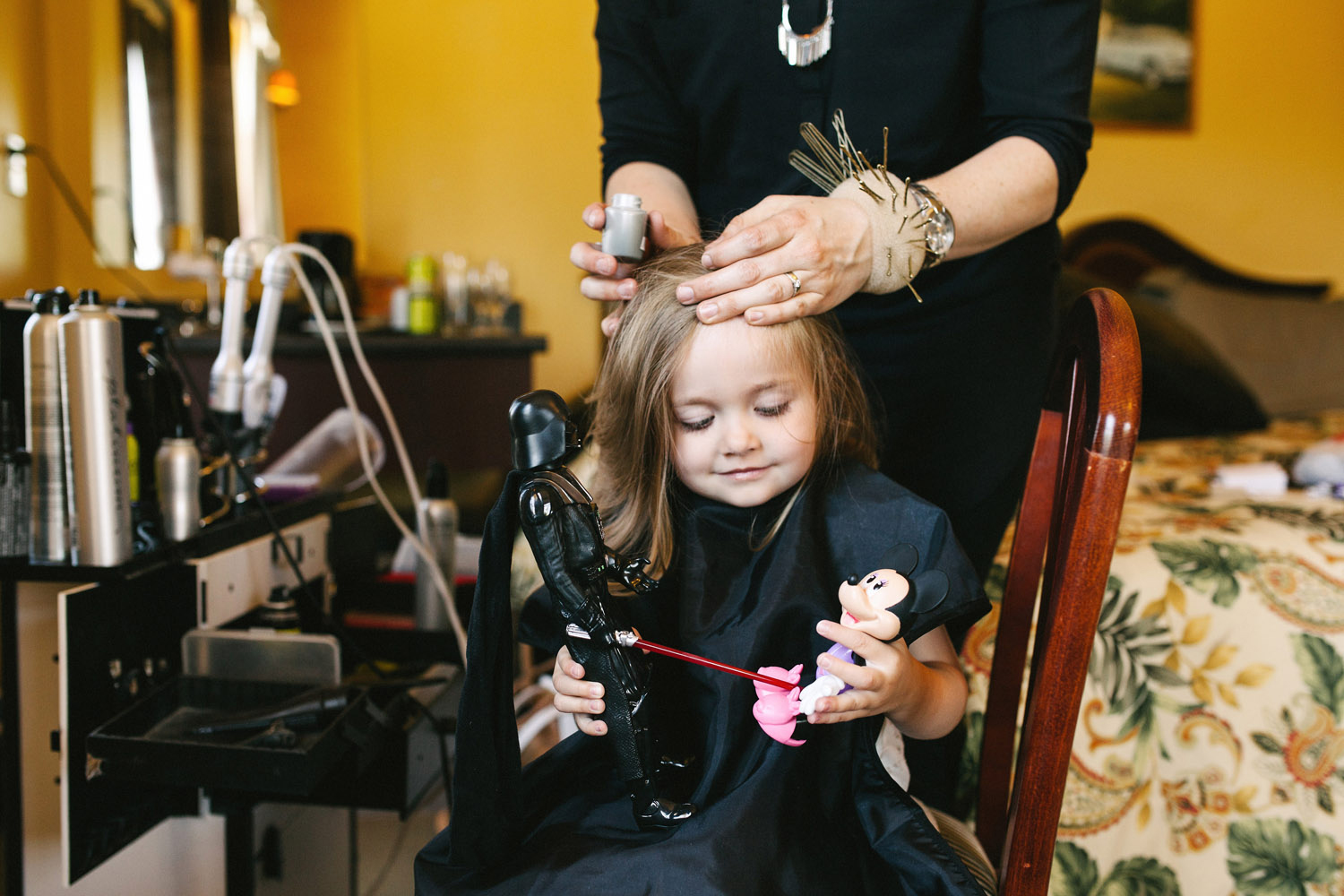 Flower girl plays with Darth Vader as she gets her hair done