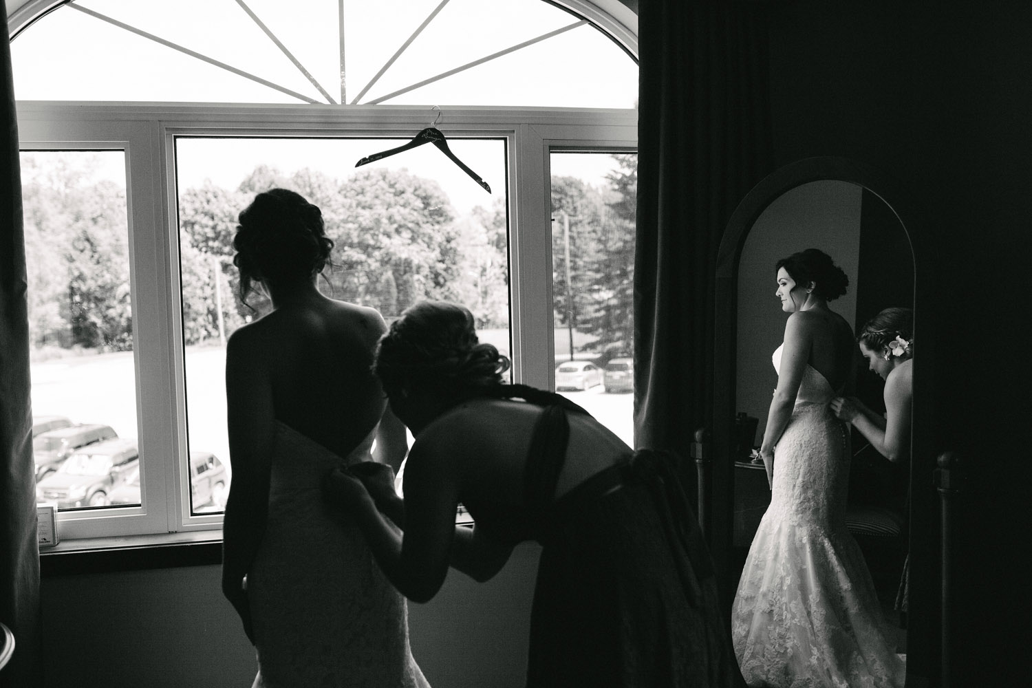 Bridesmaid helps Bride put on wedding dress at Walters Falls Inn