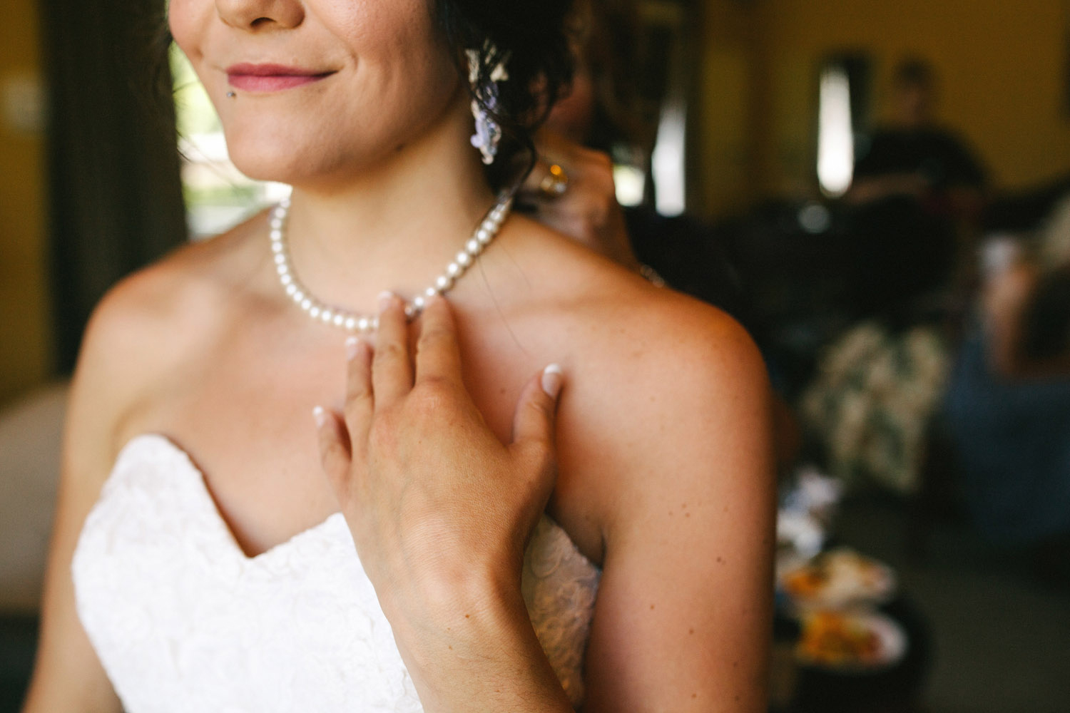 Bride touches her Grandmother's pearls