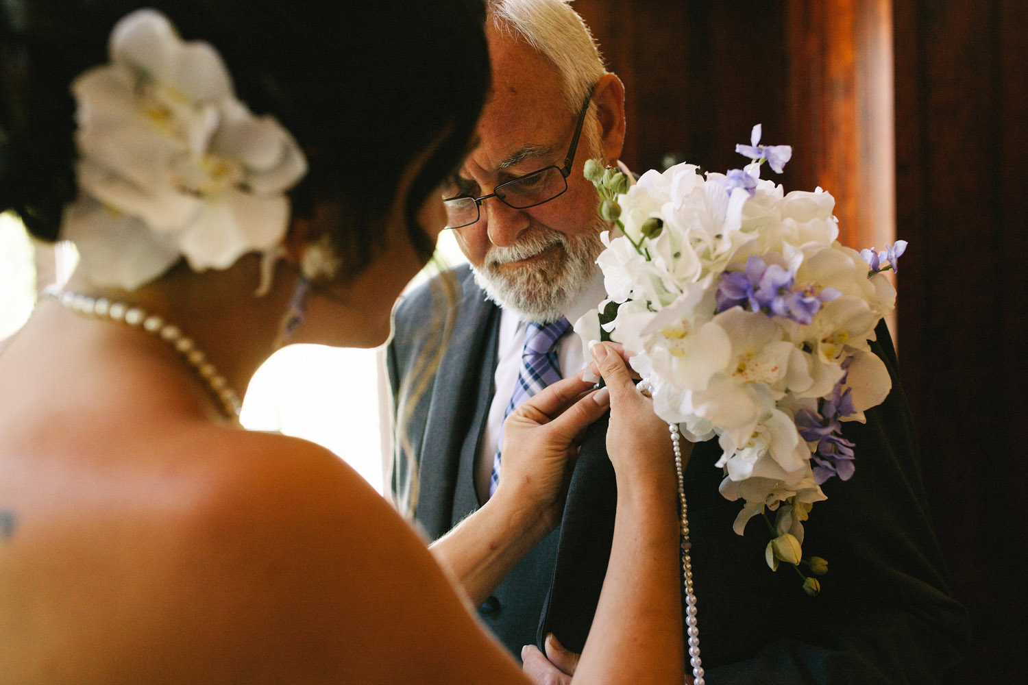 Bride pins boutinere to her father's lapel