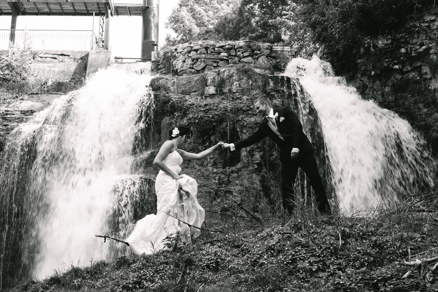 Groom helps Bride along at waterfalls
