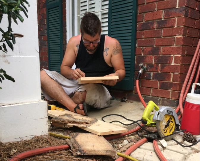Jon Potter, 29, fixing rotted porch posts in Pittsburgh for someone for free. (Courtesy of Jon Potter)