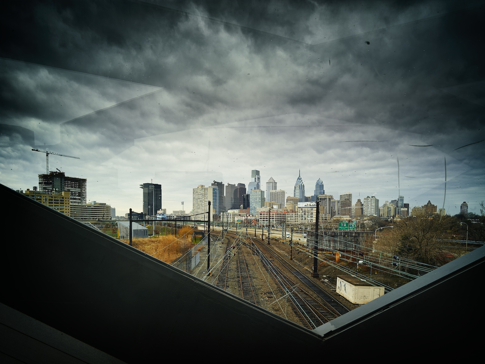 From bridge, the view back towards Philadelphia, structure reflected in sky.