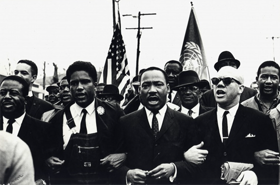 Spider Martin – Dr. King Leads The March Along With James Forman Of SNCC And Reverend Jessie Douglas Around The State Capitol In Montgomery, March 25, 1965