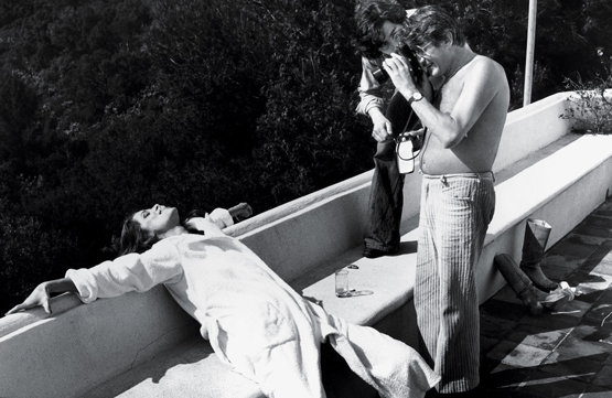 "Helmut Newton photographing Charlotte Rampling in Cannes, 1976 ""Vogue sent us to a villa high in the hills overlooking Cannes to photograph the actress Charlotte Rampling — she was the scandalous star of the moment, who had been involved in a ménage à trois with two men. Helmut was deeply impressed with her politeness and reserve, and he was taken with her lavish sensuality. He deferred to her as a little boy would. She was a different subject for him, because he was accustomed to directing inexperienced, compliant models."""