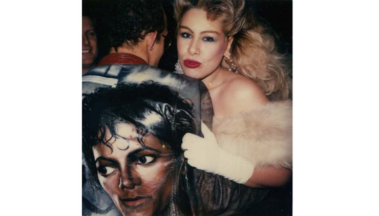 Dianne Brill with Keith Haring in a Stefano jacket, as Rudolf looks on at MoMA's reopening, May 1984, Polaroid, Trey Speegle